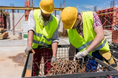 Two workers wearing yellow hard hats and safety reflective vests while checking a pile of rusty steel bars during work on the construction site stock vector