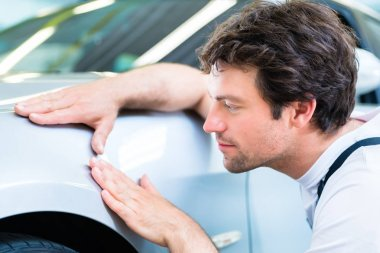 Male mechanic examine car