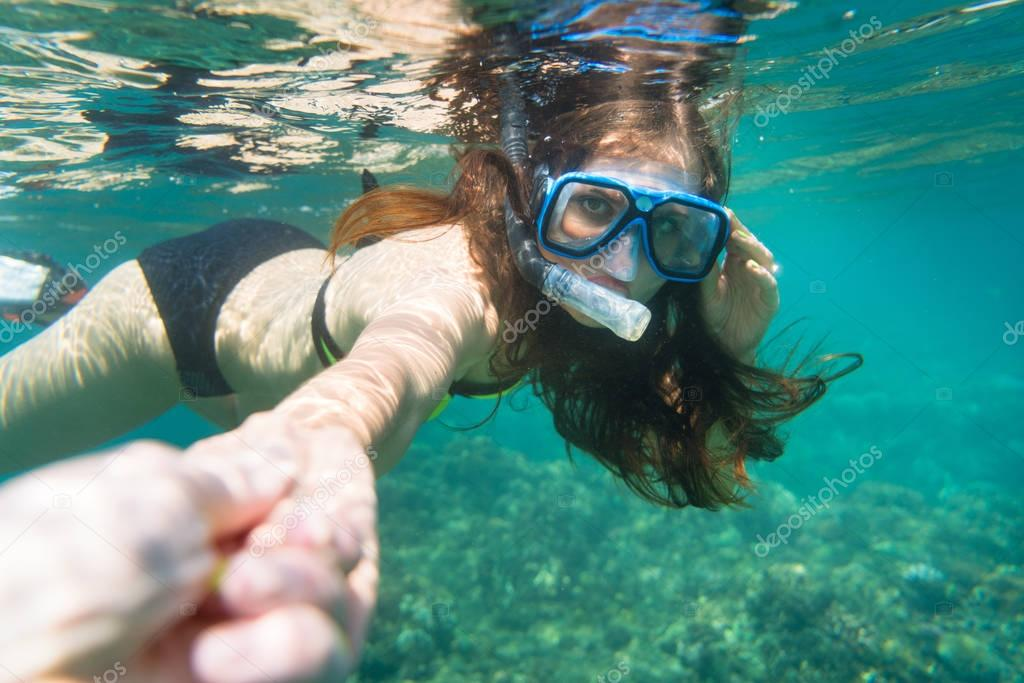 Snorkelling woman makes tempting gesture in ocean