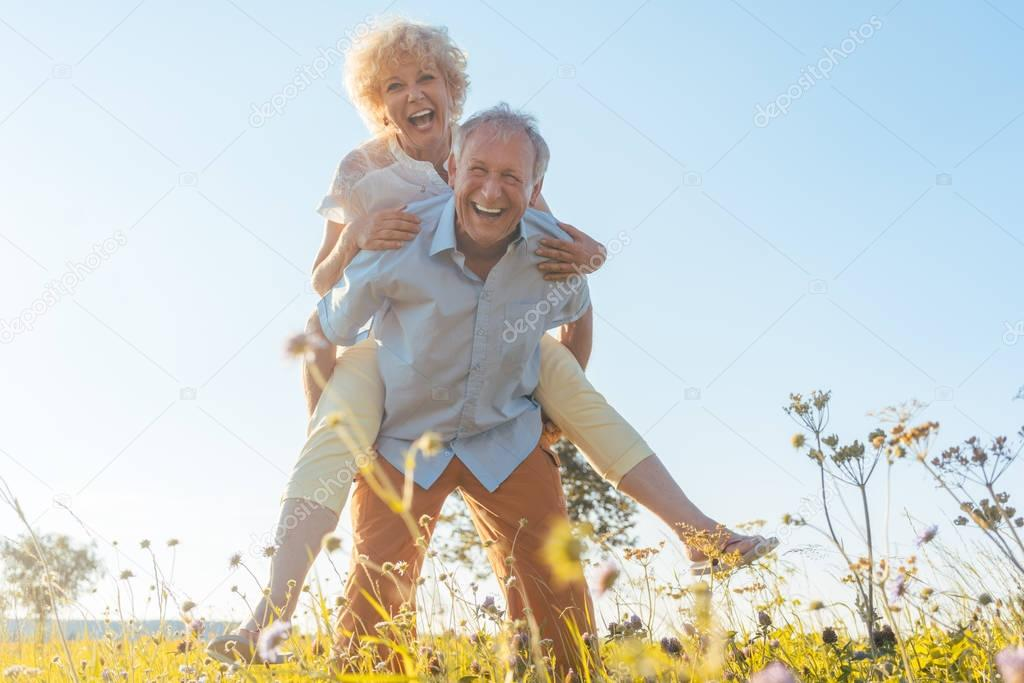 Happy senior man laughing while carrying his partner on his back