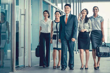 Asian business team of executives walking into office very deter