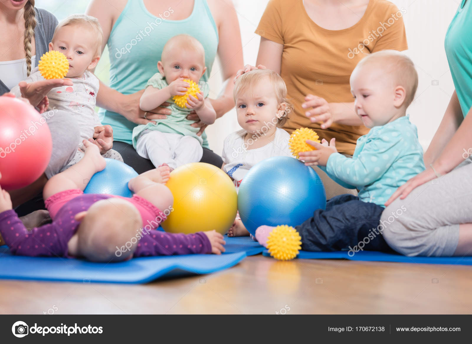 Young women in mother and child group playing with their baby ki stock photo