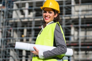 Female civil engineer with construction plans