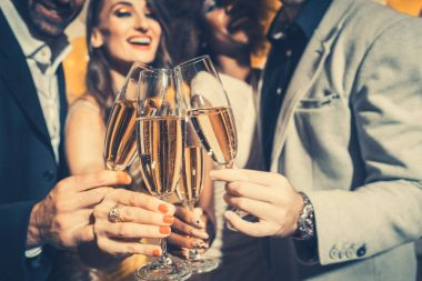 Men and women celebrating party while clinking glasses with spar