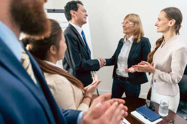 Two business managers shaking hands during meeting in the confer