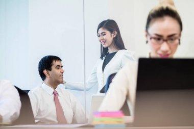 Office co-workers talking gossip behind back of businesswoman