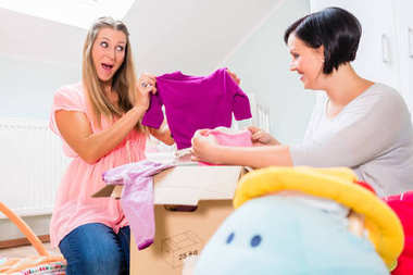 Pregnant woman and friend sharing baby clothes
