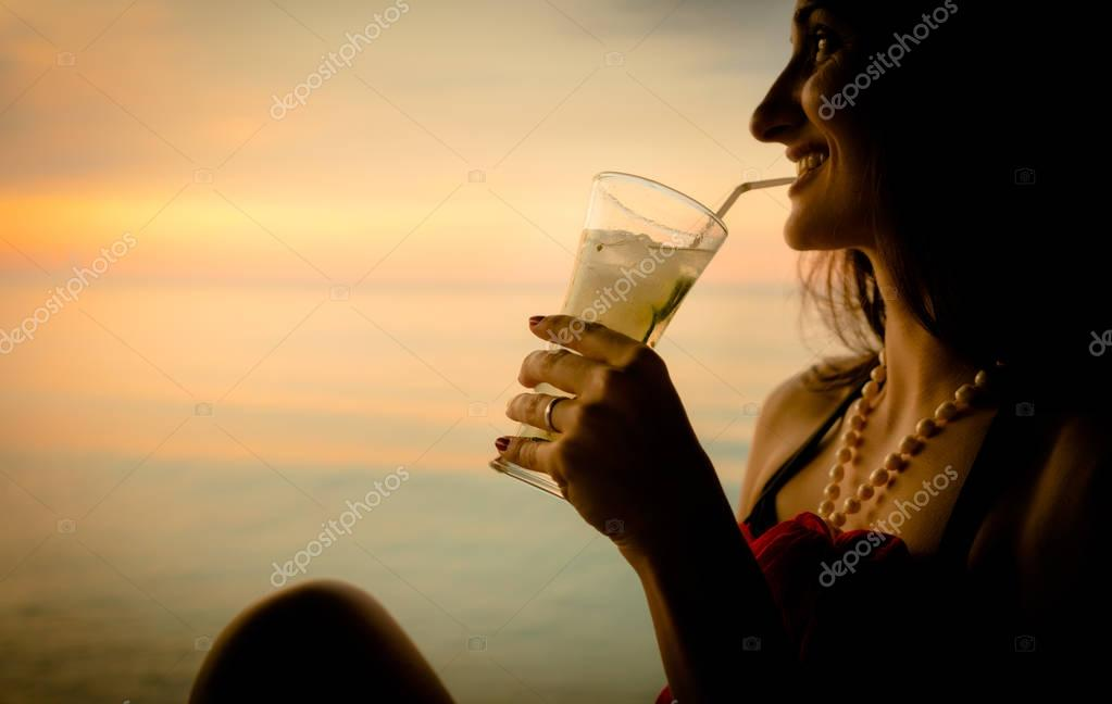 Woman tourist in summer vacation drinking cocktail at sunset