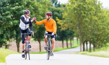 Racing cyclists after sport and giving high five