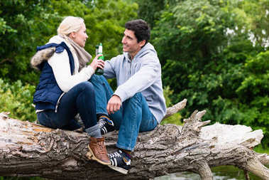 Lovers in vacation sitting at waterside clinking beer bottles