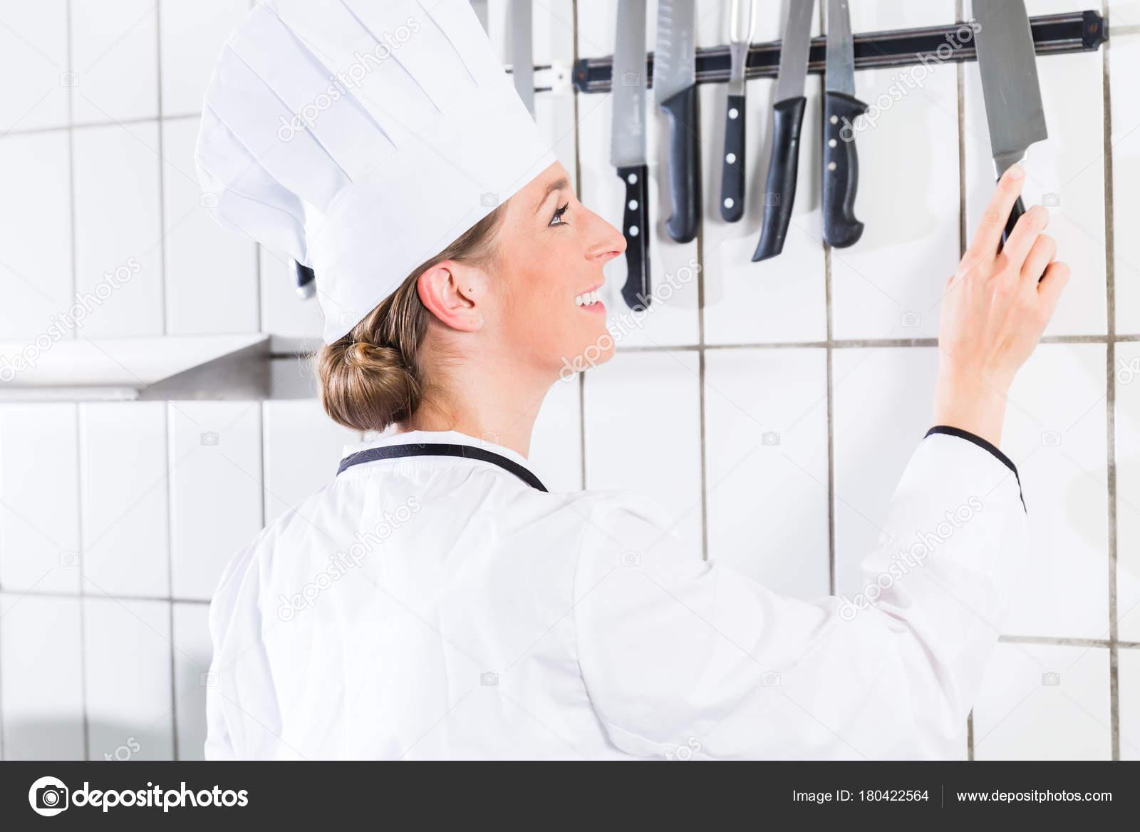 Chef Feminino Na Faca De Tomada Da Cozinha Industrial Do Suporte De