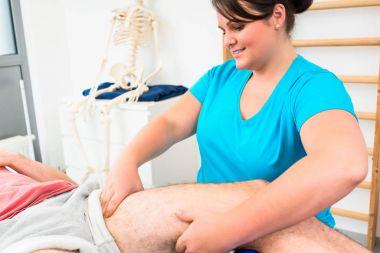 Physical therapist massages male leg