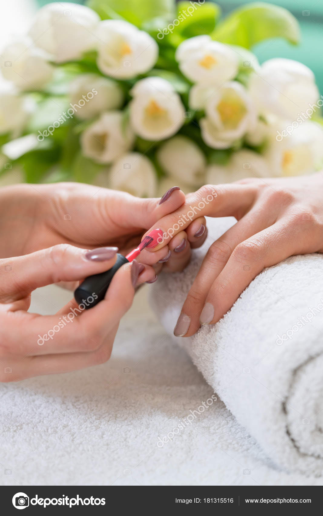 Hands of a skilled manicurist applying red nail polish on the na ...
