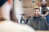 Fotografie Young man smiling while looking at his new trendy haircut in the