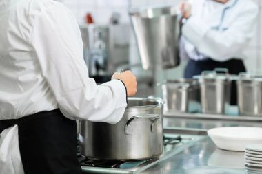 Chefs at stove in professional catering kitchen stirring in pots
