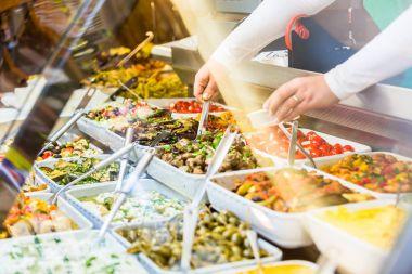Woman selling Meze appetizers in delicatessen shop