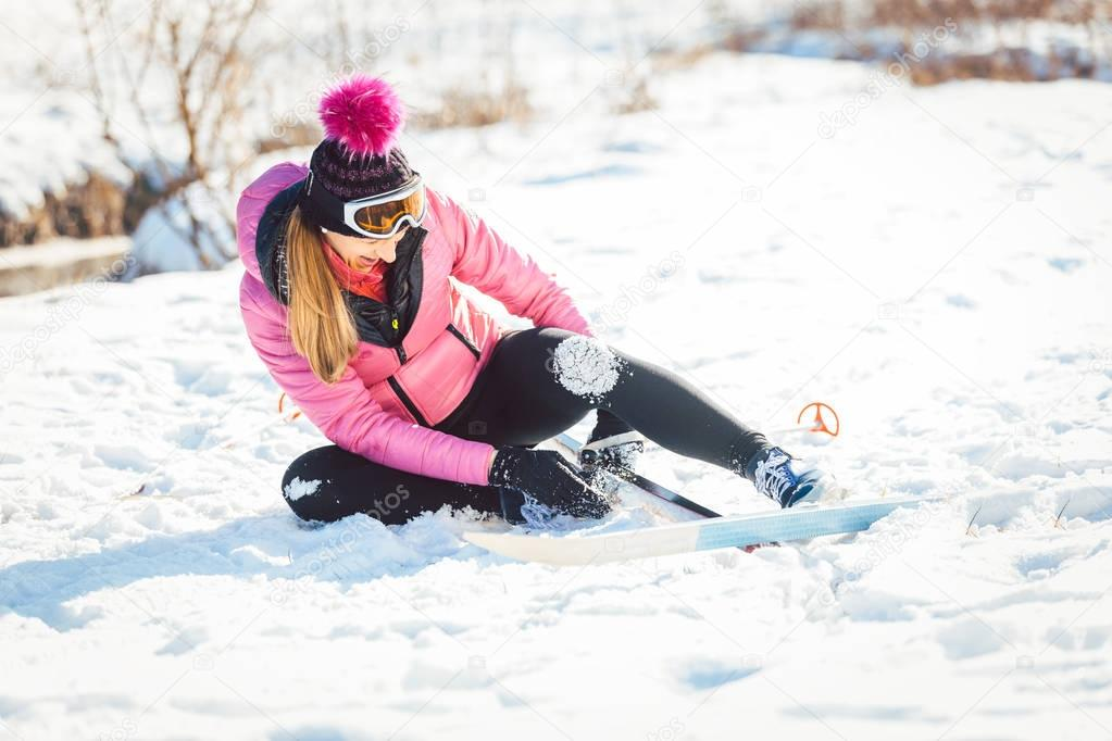 Woman falling while doing cross country skiing as a sport
