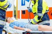 Photo Emergency doctors putting injured boy in ambulance