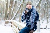 Fotografia Donna che si congela giorno di inverno freddo riscaldando con la bevanda calda