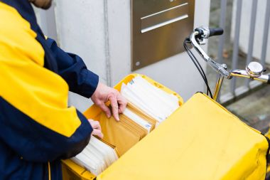 Postman delivering letters to recipient mailbox