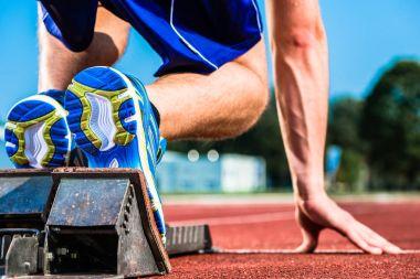 Runner before start signal on starting block of sprint track