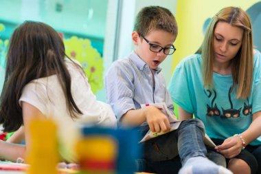 Pre-school boy learning to read helped by a kindergarten teacher assistant