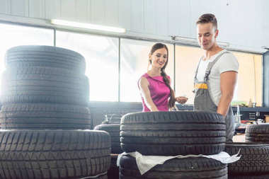 Handsome auto mechanic helping a customer to choose from various tires