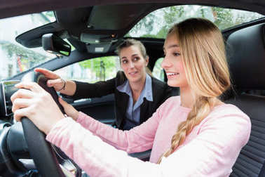 Student on wheel of car in driving lesson with her teacher