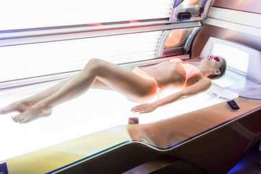 Beautiful woman lying down on an horizontal bed for indoor tanning