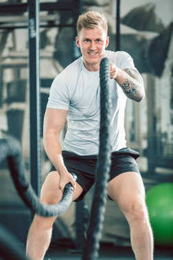 bodybuilder exercising with heavy battle ropes during intense functional training workout in gym