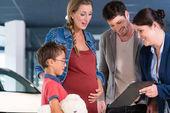 Fotografie Familie Preis für Neuwagen mit der Verkäuferin diskutieren