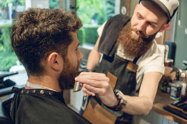 Close-up side view of a handsome redhead young man sitting on the chair of a trendy barbershop for trimming and styling his beard