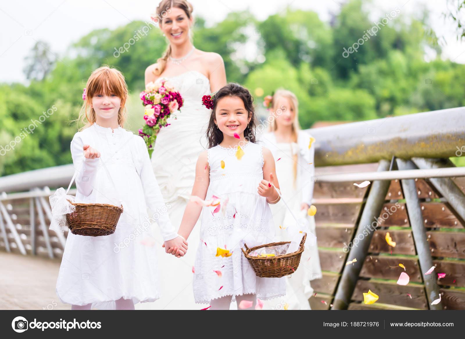 Braut im Hochzeitskleid mit Brautjungfern auf Brücke — Stockfoto ...