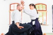 Fotografie Man and woman fighting at Aikido martial arts school