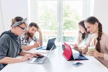 Dedicated young women editing document on laptops while sharing desk with other hard-working co-workers in modern office space for digital nomads