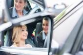 Student v autoškole za volantem automobilu s její instruktor učí řídit