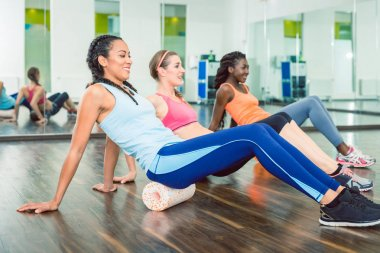 Side view of a fit beautiful woman smiling, while exercising on versatile foam roller during group workout class at a trendy fitness club with modern equipment