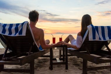 Young couple drinking cocktails on a beach at sunset during vacation
