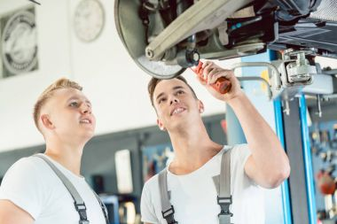 Experienced auto mechanic teaching an apprentice about disk brakes