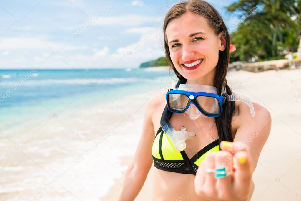 Girl on vacation in bikini with swim fins and diving goggles walks along beach