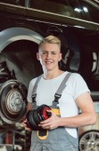 Photo Portrait of a confident young auto mechanic holding a new air suspension system