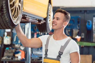 Portrait of a car tuning specialist smiling while checking wheels of tuned car