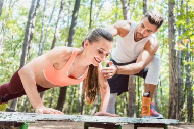 Sporty woman doing push-up in an outdoor gym, her boyfriend is watching her