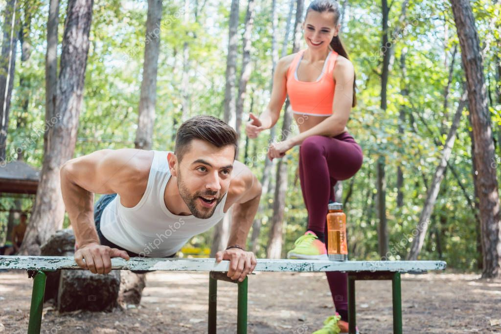 Sporty man doing push-up in an outdoor gym, his girlfriend is watching him