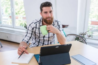 Portrait of a confident self-employed young man sitting at desk