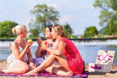 Women eating fruit at river beach picnic
