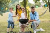 Portrét šťastné rodiny s dětmi představují za grilování