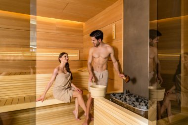 Young couple in love smiling while relaxing together in a dry sauna