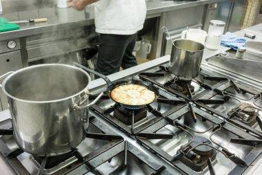 Apple pie in pan on stove in restaurant kitchen