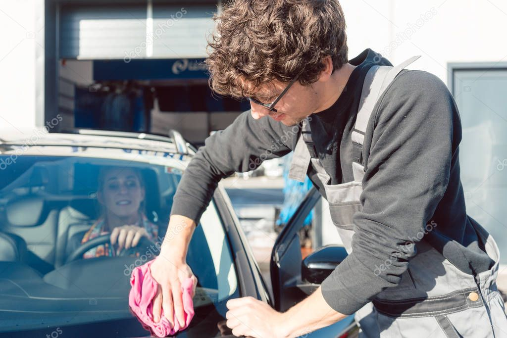 Diligent service man helping woman cleaning her car in commercial wash